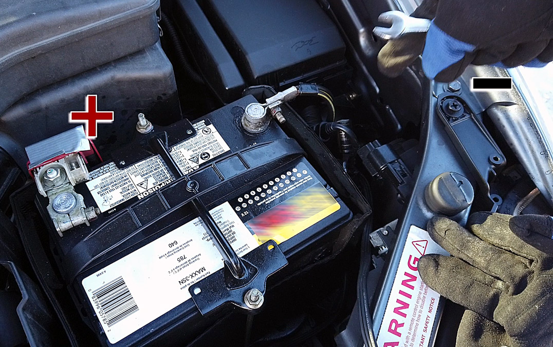 Engine bay showing 12V car battery and car body as ground/negative