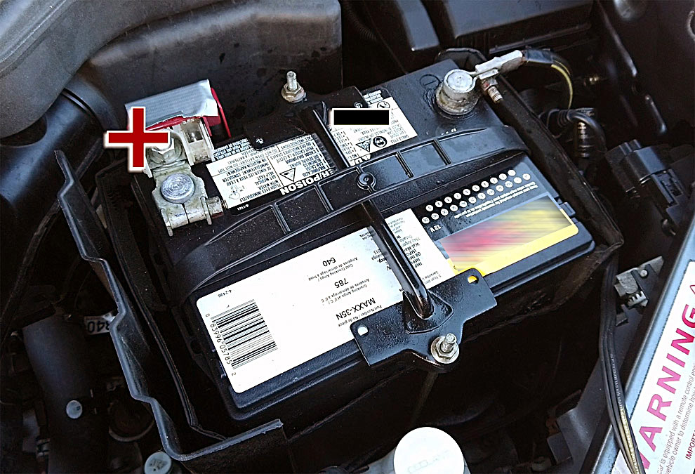 Engine bay showing 12V car battery and metal battery bracket as ground/negative
