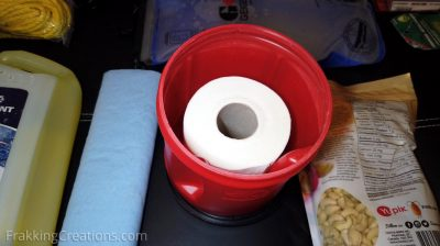 Toilet paper with re-used plastic container storage for car emergency kit