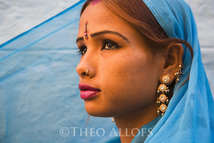 Rajasthani girl in blue dress and traditional Rajasthani jewelry in front of blue house wall in Jaisalmer Fort