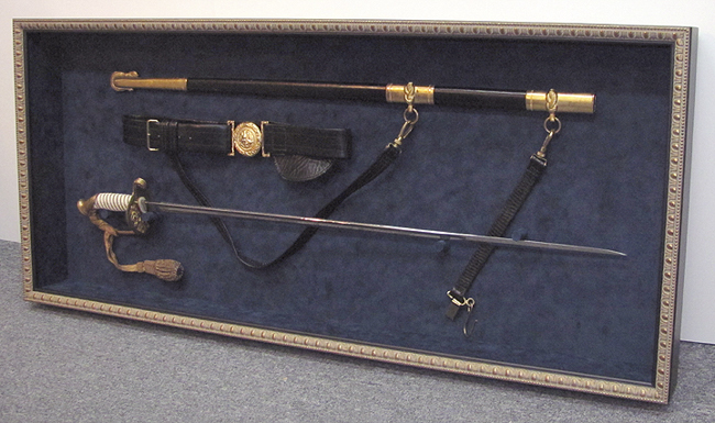 This is a Vietnam era Navy Officer's sword and scabbard, in a classic gold and black shadowbox with navy blue suede background. Hand sewn and wired in place, with custom wrapped mounts and UV filtering, low reflection Museum glass. We're especially honored to have framed this one, because it belongs to Ida's dad, Paul!