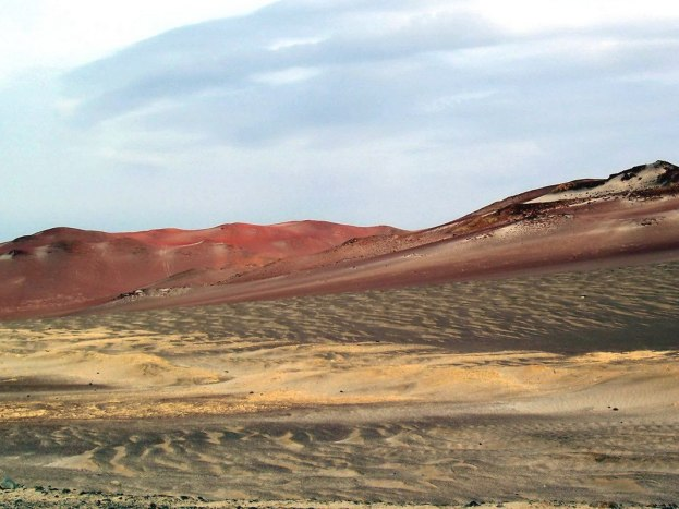 Red burnt desert hills at Paracas National Reserve on the Paracas Peninsula, Ica, Peru.