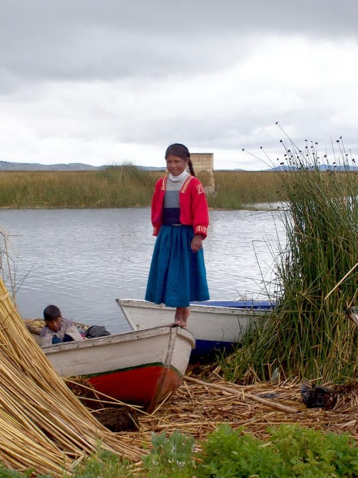 Uros girl stands on a boat on a floating island on Lake Titicaca in Peru, South America