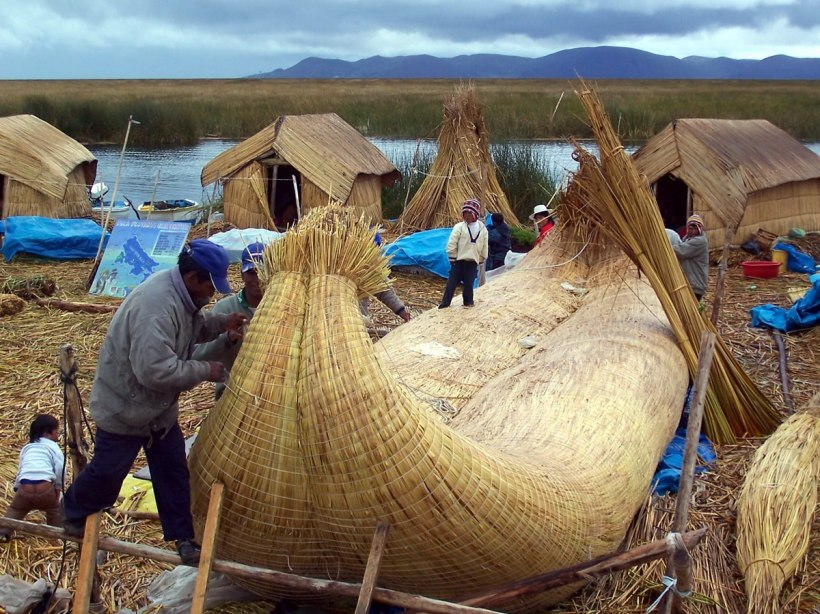 Uros men construct a reed boat on a floating island on Lake Titicaca in Peru, South America