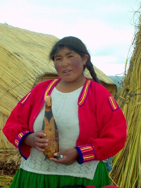 uros woman holds carving, floating island, lake titicaca, peru