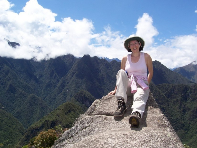 Jean sitting on the pinnacle of Huayna Picchu, at Machu Picchu