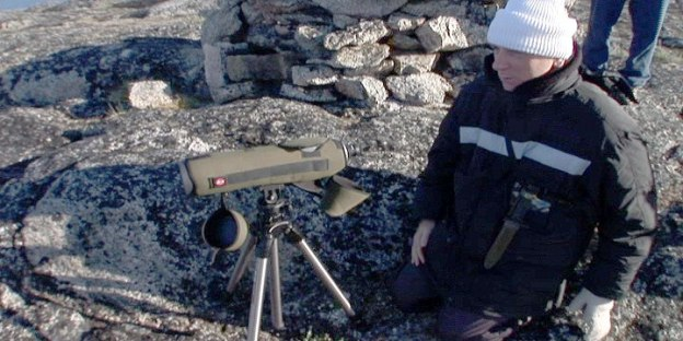 Bob using telescope to searches for Bowhead whales off Kekerten Island in the Cumberland Sound, off Baffin Island, Nunavut, Canada