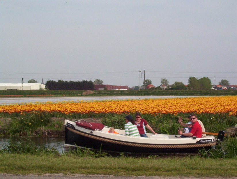An image of a small boat on a canal beside a field of tulips near Lisse, in the Netherlands. Photography by Frame To Frame - Bob and Jean.