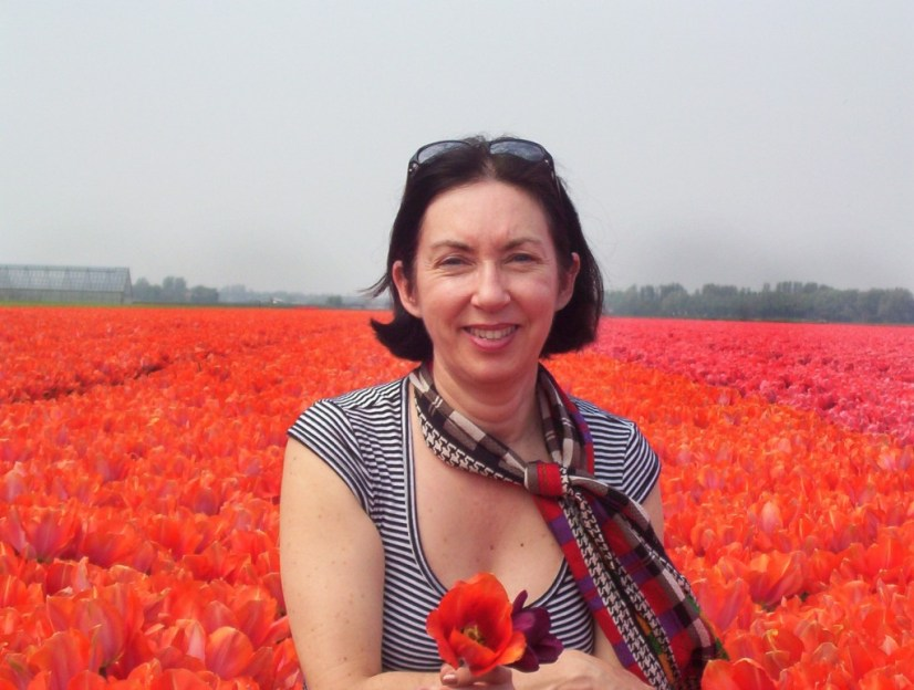 An image of Jean holding two tulips as she stands beside a field of orange tulips near Lisse in the Netherlands. Photography by Frame To Frame - Bob and Jean.