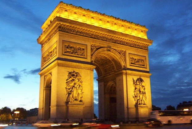 An image of the Arc de Triomphe at sunset in Paris, France.