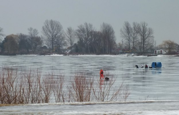 Ice fishermen heads out on ice - Frenchman's Bay - Ontario - Canada
