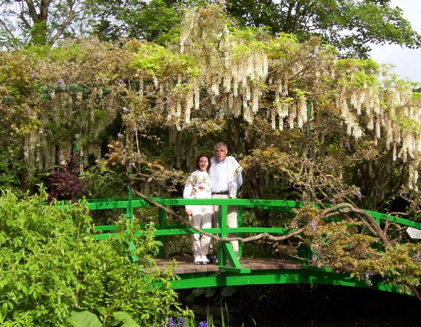 An image of Jean and Bob standing on the green bridge over Monet's Water Lily Pond in Giverny, France.