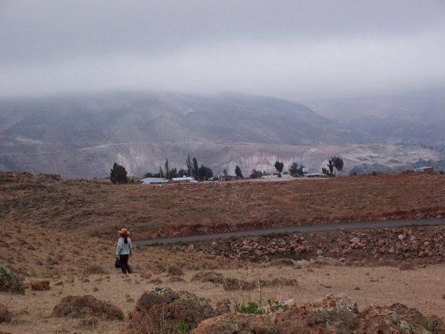 Young girl walks across the countryside near Nazca, Peru