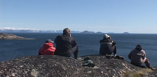 group searches for whales with binoculars - kekerten island - nunavut