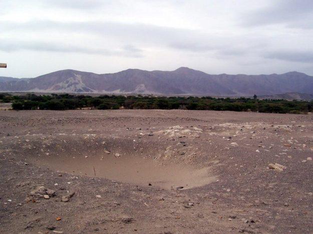 A pit in the desert at the Chauhilla Cemetery near Nazca in Peru, South America.