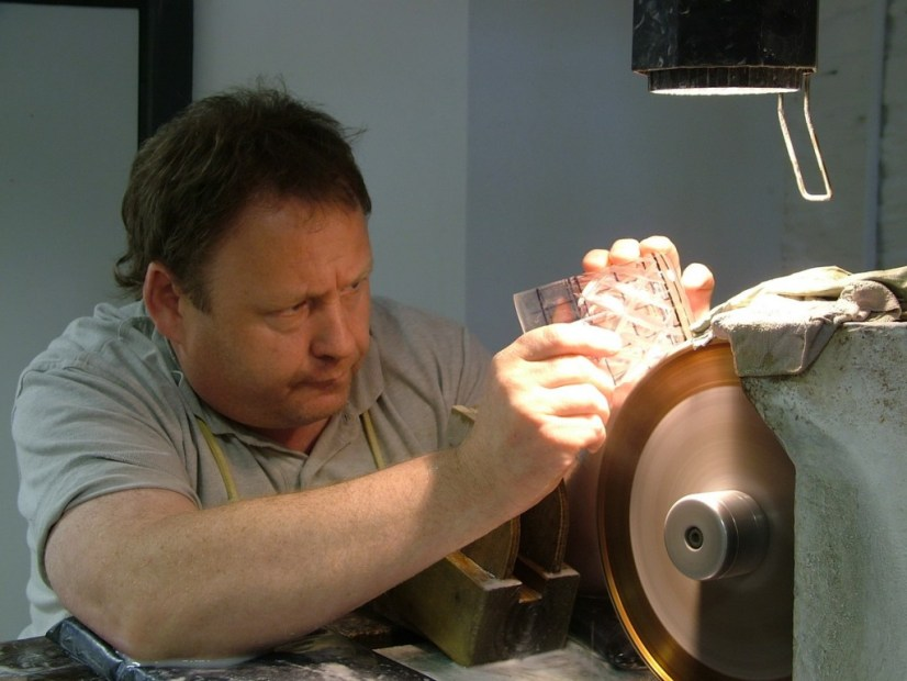 An image of a glass cutter, cutting a crystal goblet at the Waterford Crystal factory in Waterford, Ireland. Photography by Frame To Frame - Bob and Jean.