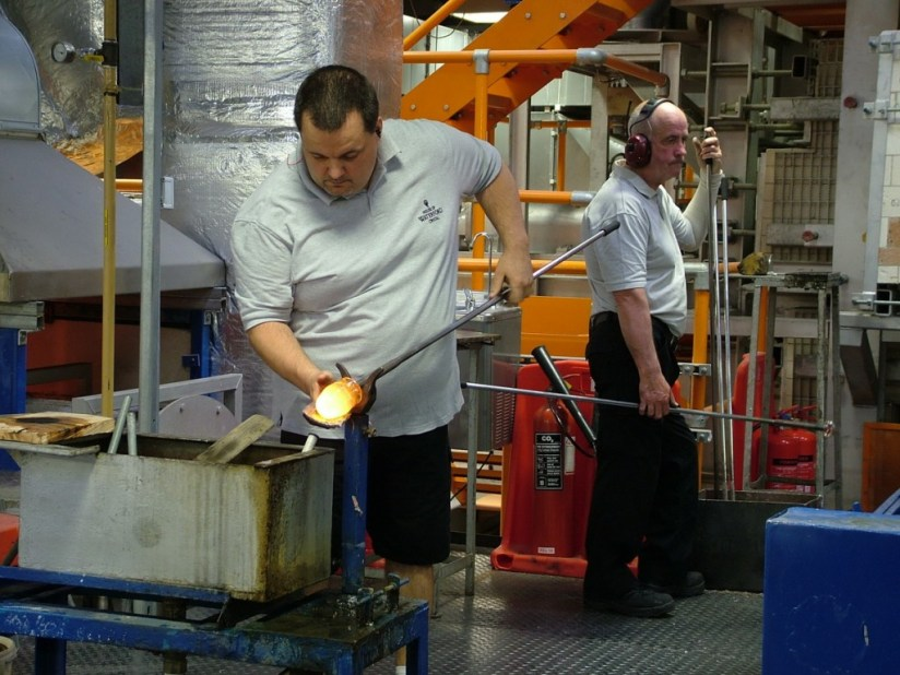 An image of a glass blower working with molten glass at the Waterford Crystal factory in Waterford, Ireland. Photography by Frame To Frame - Bob and Jean.
