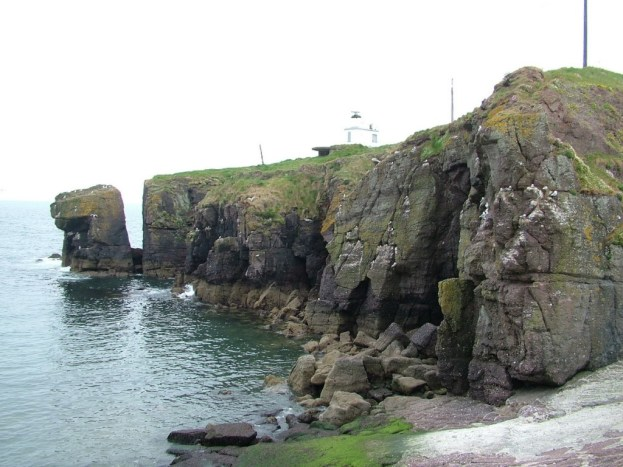 rock cliffs along shoreline at dunmore east in county waterford - ireland