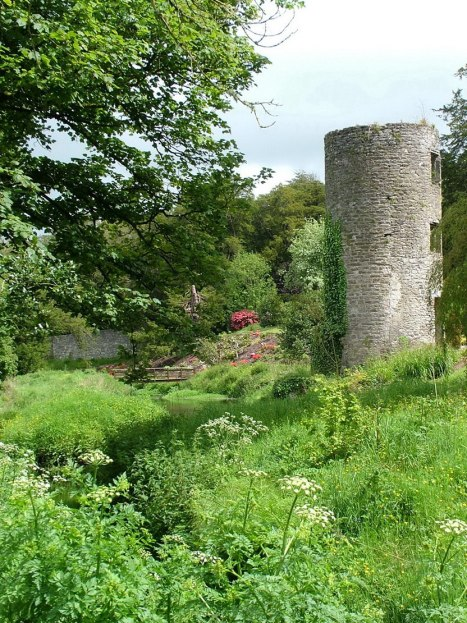 An image of a stone tower beside gardens and a stream at Blarney Castle in County Cork, Ireland.   Photography by Frame To Frame - Bob and Jean.
