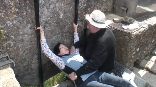 jean holds on and leans back to kiss the blarney stone, ireland