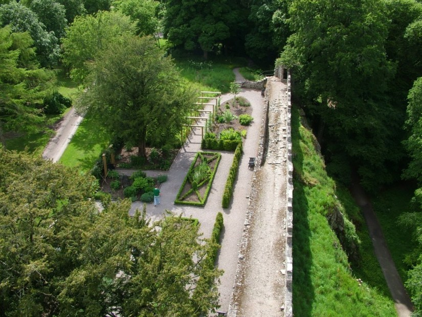 An image of the garden beds in the Poison Garden at Blarney Castle from high above on the castle's battlements in Ireland. Photograph by Frame To Frame - Bob and Jean