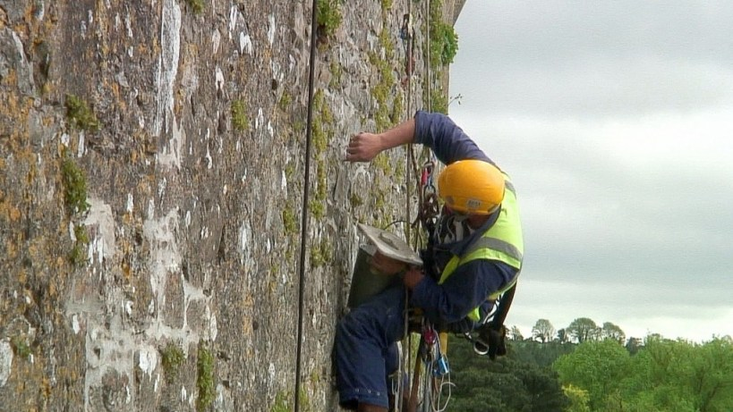 stone mason adds mortar to outer wall of blarney castle, ireland