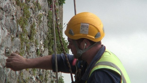 stone mason repairs outer wall of blarney castle, ireland