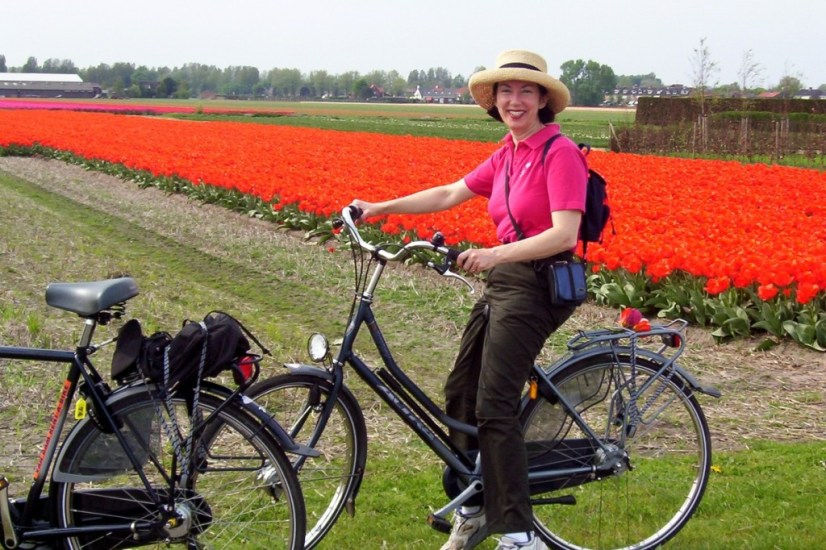 An image of Jean on a rental bicycle beside a tulip field near Lisse in the Netherlands. Photography by Frame To Frame - Bob and Jean.