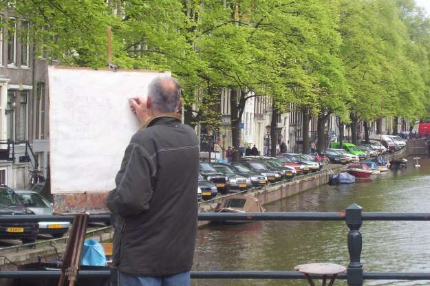 artist paints on canal in amsterdam