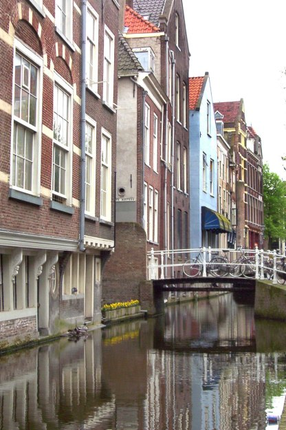 buildings and bikes along canal - delft - the netherlands