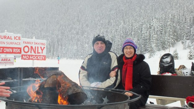 Jean and Bob at the lakeside fire at Chateau Lake Louise on Lake Louise in the winter, Banff National Park, Alberta, Canada