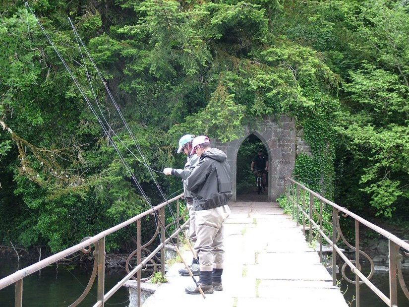 An image of fly fishermen with their rods on the Cong Canal bridge near the Royal Abbey of Cong, in Cong, Ireland. Photography by Frame To Frame - Bob and Jean.