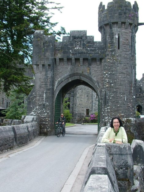 An image of Jean standing on the the stone bridge with castle turrets at Ashford Castle on the Cong Canal in County Mayo, Ireland. Photography by Frame To Frame - Bob and Jean.