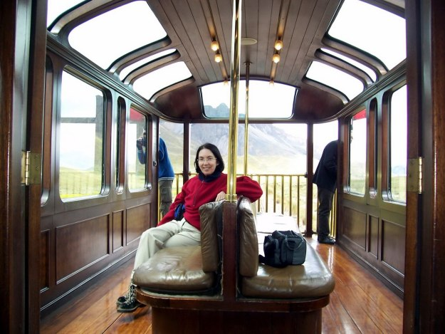 Jean sitting in the PeruRail Andean Explorer open-air observation car in Peru, South America