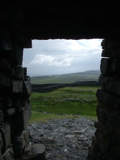 An image of the view of Inishmore Island through a doorway in the stone walls of Dun Aonghasa Fort in Ireland. Photography by Frame To Frame - Bob and Jean.
