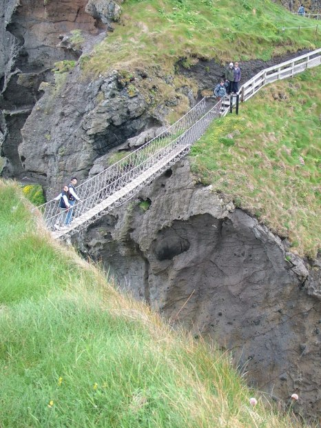An image of people walking on the Carrick-a-Rede rope bridge near Ballintoy in County Antrim, Northern Ireland. Photography by Frame To Frame - Bob and Jean.
