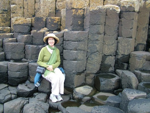 An image of Jean sitting on one of the hexagonal basalt columns at the Giant's Causeway, near Portrush, Northern Ireland. Photography by Frame To Frame - Bob and Jean.