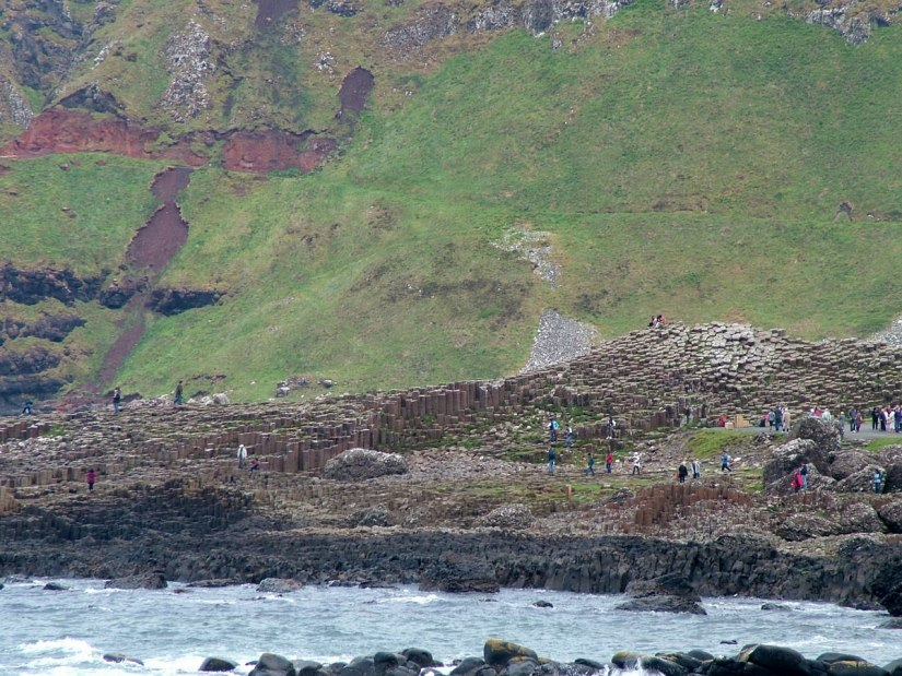 An image of people walking on the polygonal basalt columns at the Giant's Causeway in Northern Ireland. Photography by Frame To Frame - Bob and Jean.