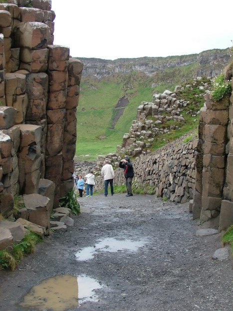 An image of people walking on a pathway through the hexagonal basalt columns at the Giant's Causeway, near Portrush, Northern Ireland. Photography by Frame To Frame - Bob and Jean.Photography by Frame To Frame - Bob and Jean.