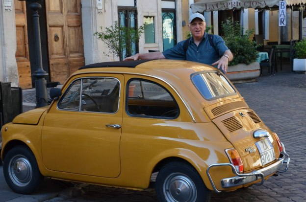 Bob beside a yellow Fiat in Rome, Italy
