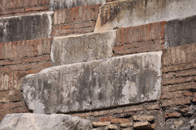 An image of inscriptions carved on marble blocks at the Colosseum in Rome, Italy.   Photography by Frame To Frame - Bob and Jean.