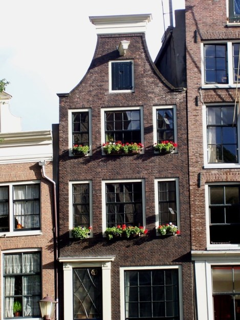 row house along canal in amsterdam