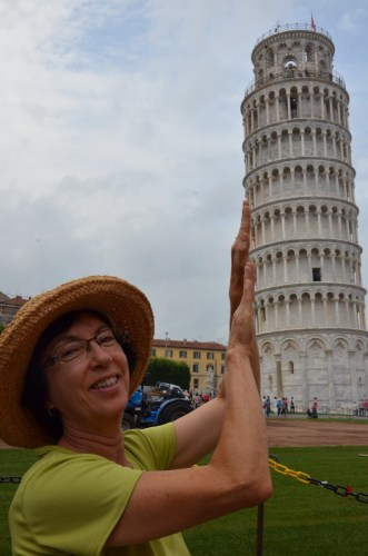 An image of Jean pretending to hold up the Leaning Tower of Pisa in Tuscany, Italy. Photography by Frame To Frame - Bob and Jean.