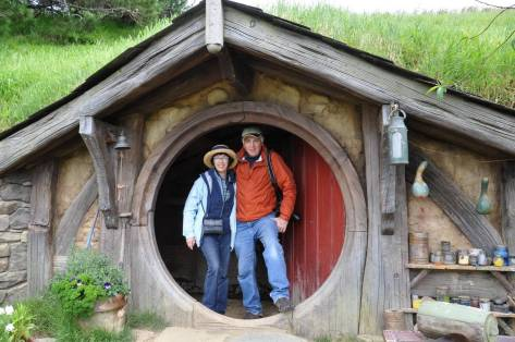 An image of Bob and Jean standing in the doorway of the gourd artists hobbit hole at Hobbiton in New Zealand. Photography by Frame To Frame - Bob and Jean.