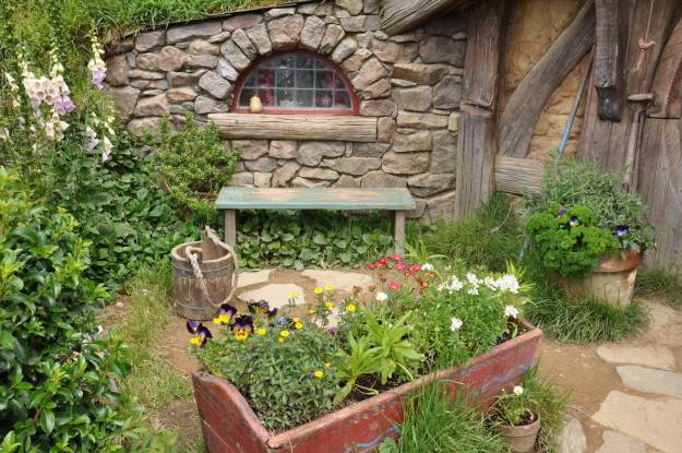 An image of the flower gardens and a stone window in the Gourd Artists home at Hobbiton in New Zealand. Photography by Frame To Frame - Bob and Jean.