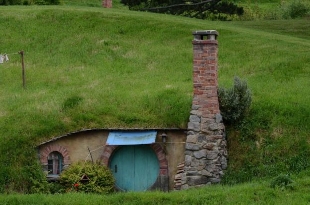 An image of a hobbit hole with a blue door and a tall chimney at Hobbiton in New Zealand. Photography by Frame To Frame - Bob and Jean.