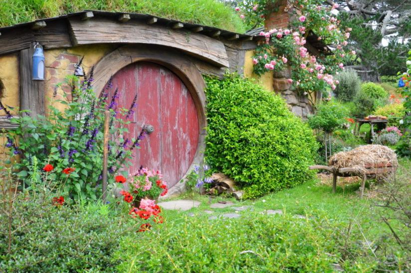 An image of a hobbit hole with a red door at Hobbiton, in New Zealand. Photography by Frame To Frame - Bob and Jean.