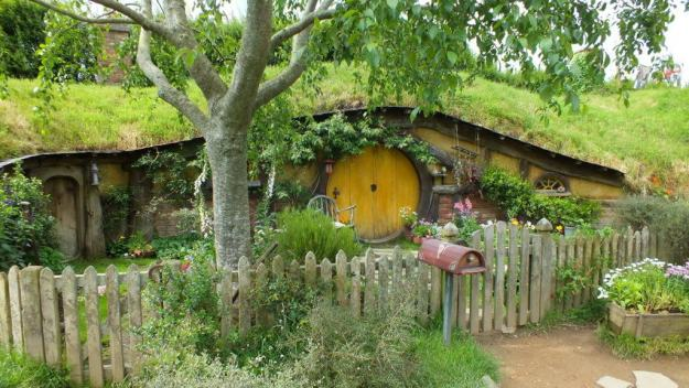 An image of a hobbit hole with a yellow door and a wooden fence with a gate out front of it at Hobbiton, in New Zealand. Photography by Frame To Frame - Bob and Jean.