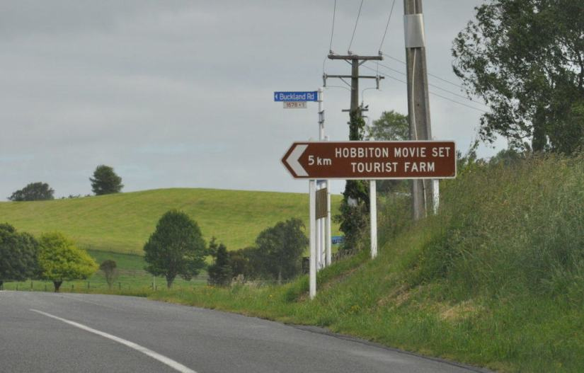 An image of the 5 km highway sign giving directions to the Hobbiton Movie Set Tourist Farm in New Zealand. Photography by Frame To Frame - Bob and Jean.
