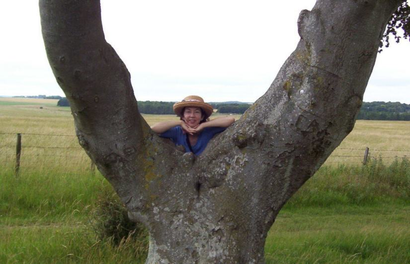 An image of Jean standing beside a Y shaped tree near Stonehenge in Wiltshire, England. Photography by Frame To Frame - Bob and Jean